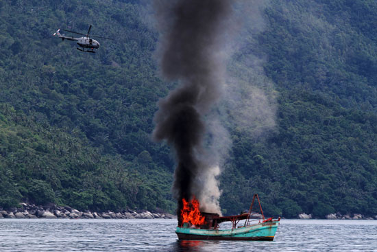 Indonesian forces sink a Vietnamese fishing boat, December 2014.