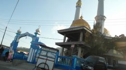 A gold-dombed mosque rising between two churches in Bajawa, in largely Catholic Flores
