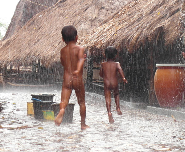 Kids in Tarong village, West Sumba, play in the rain