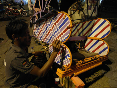 A Jokowi supporter paints his becak in the new  president's trademark check