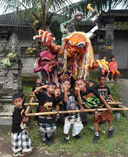 Balinese boys flick gang symbols before parading thir evil spirits around town