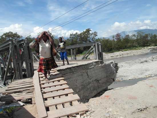 A woman carries vegetables to market across a half-collapsed bridge in Wamena, Papua, Indonesia