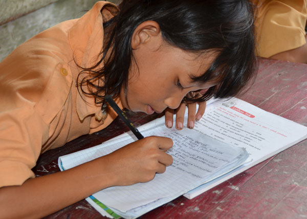 An Indonesian schoolgirl copies ut her text book